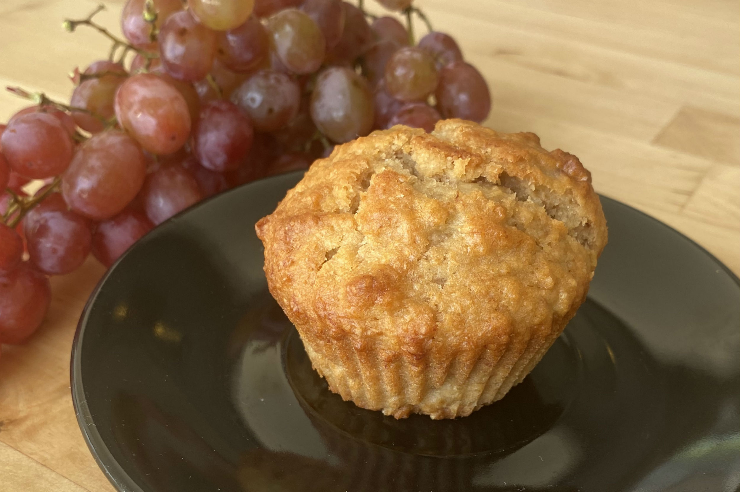 banana muffin on black saucer with grapes beside it