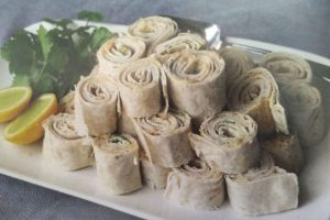 rolled flat bread with chicken filling piled on plate with lemon and parsley garnish