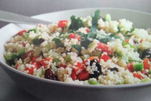 cous cous salad in a bowl with a fork