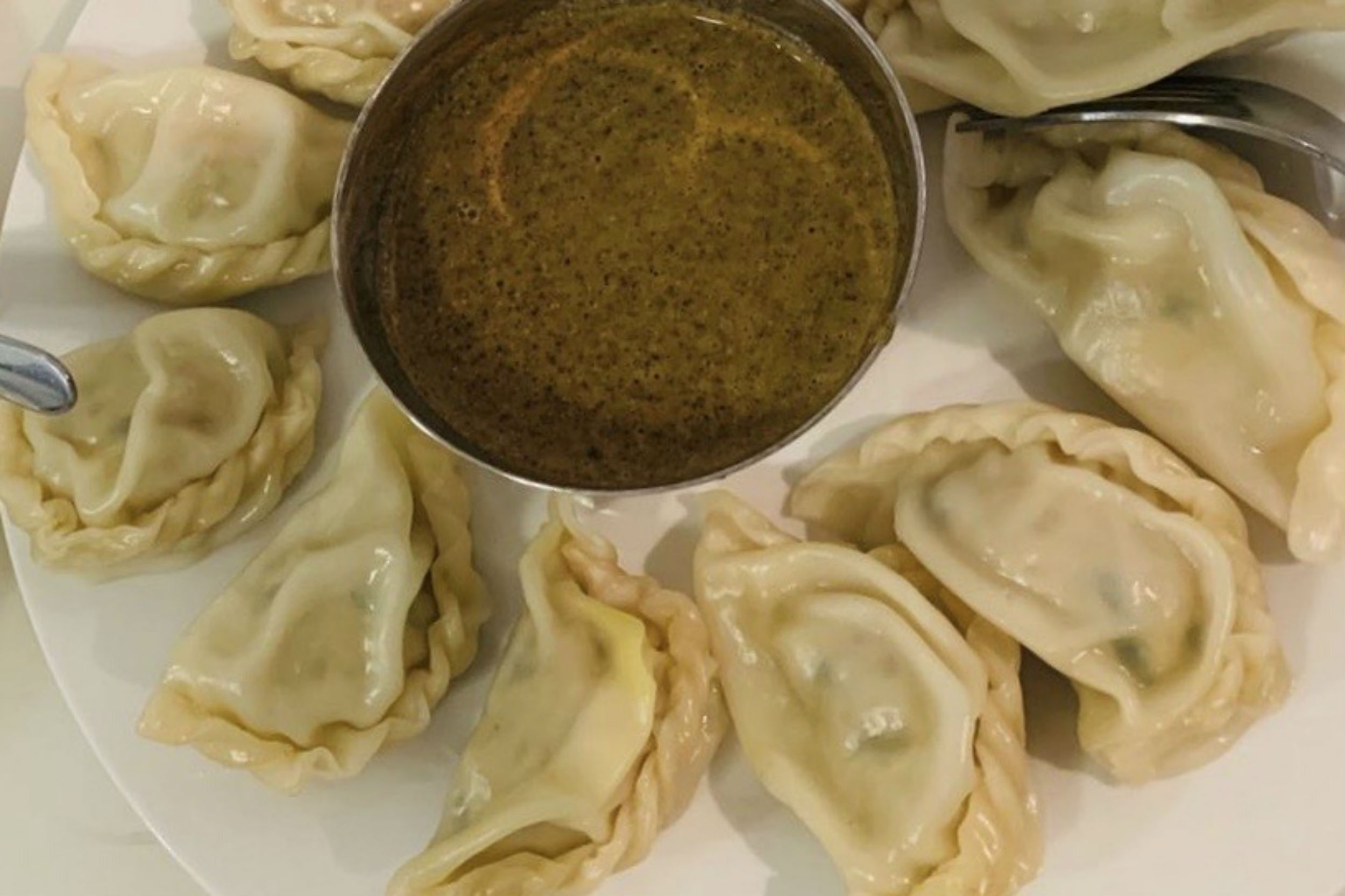 momo Nepalese dumplings on plate with dipping sauce