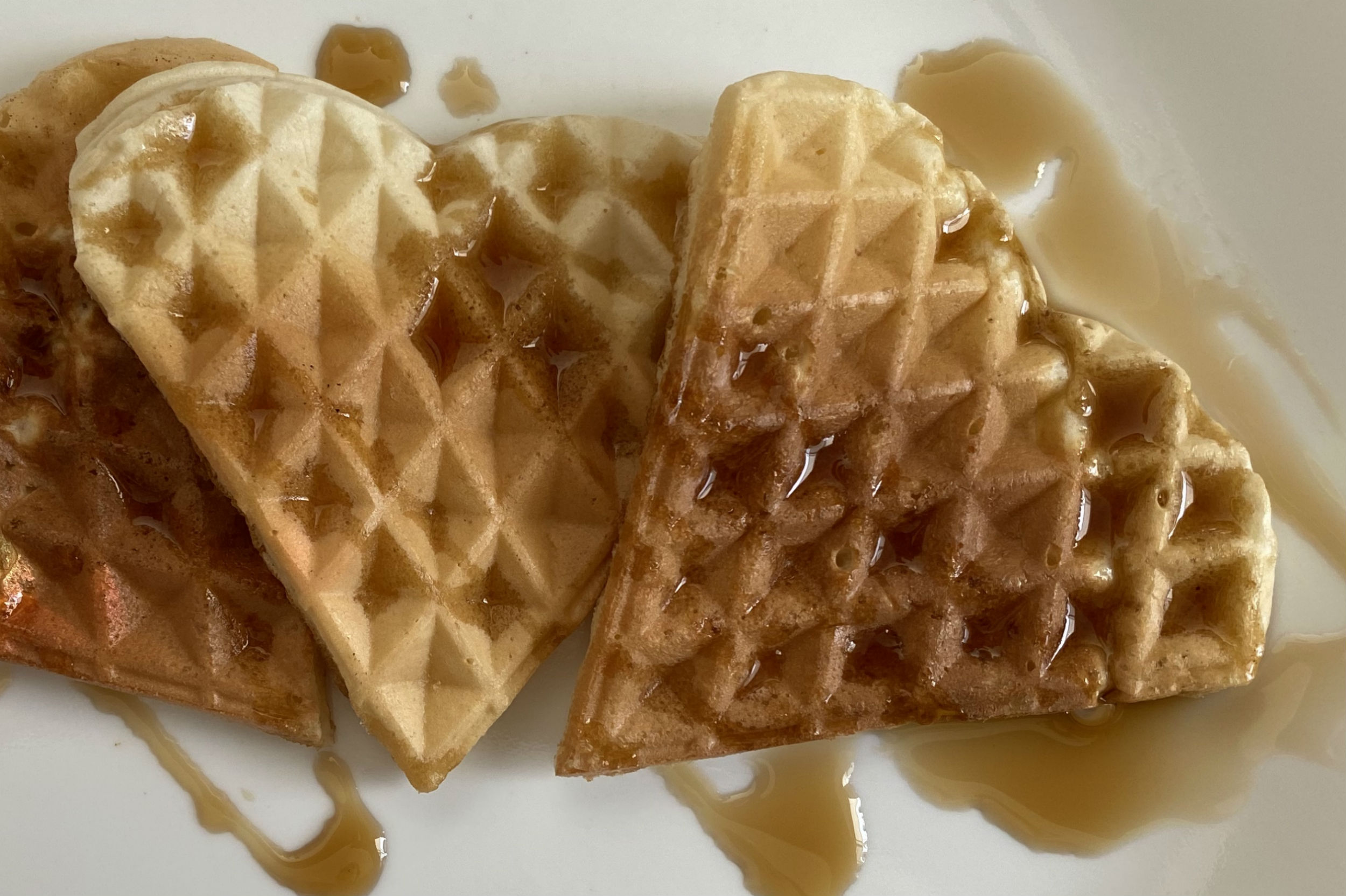 heart shaped waffles on plate drizzled with maple syrup