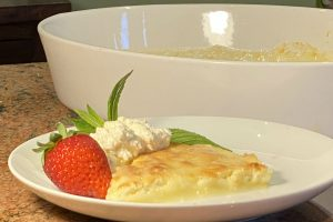 Lemon delicious pudding on a plate with strawberry and cream