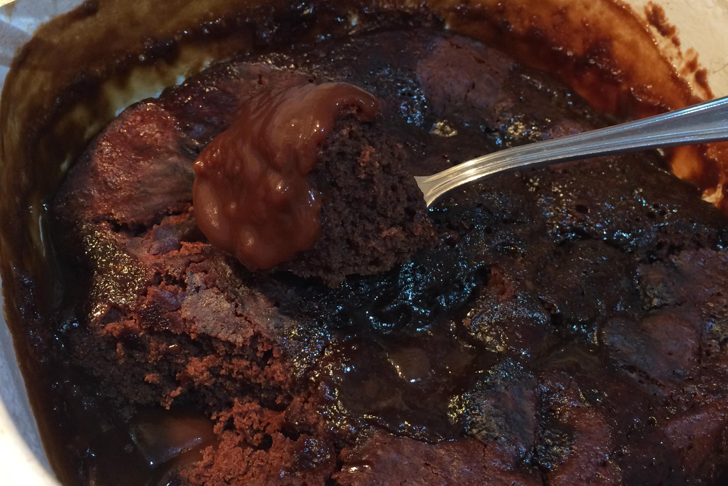 chocolate self-saucing pudding in oven dish with metal spoon