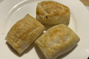 three small chicken sausage rolls on a plate